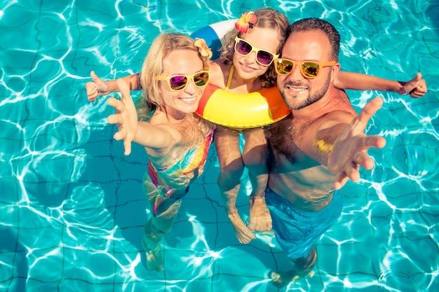 Famille heureuse avec des lunettes de soleil et des fleurs sur les cheveux avec gonflable coloré dans la piscine