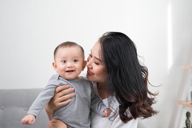 Famille heureuse à la maison. mère tenant sa petite fille dans le salon dans un agréable matin de week-end