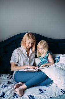 Une famille heureuse de maman blonde et sa fille lisent un livre au lit.