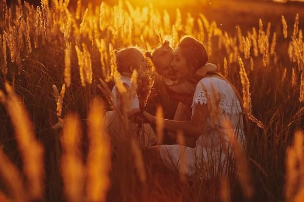 Famille heureuse, maman et deux filles. mère et fille au coucher du soleil dans la forêt. notion de famille. mère joue avec sa fille dans la rue dans le parc au coucher du soleil.