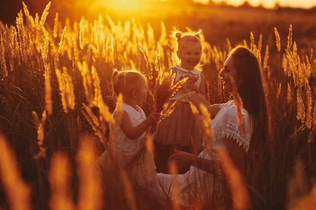 Famille heureuse, maman et deux filles. mère joue avec sa fille dans la rue au coucher du soleil. concept de famille