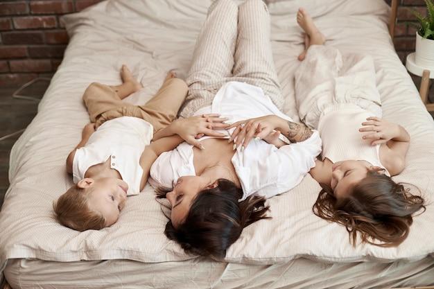 Famille heureuse. maman embrasse son fils et sa fille, mon amour. joyeuses émotions joyeuses sur le visage d'une femme, d'un garçon et d'une fille. loisirs en famille