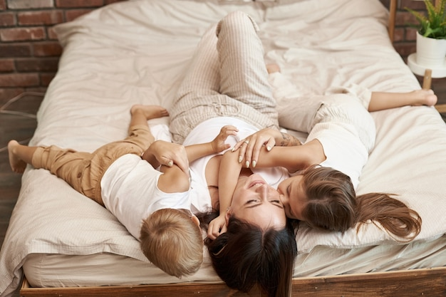 Famille heureuse. maman embrasse son fils et sa fille