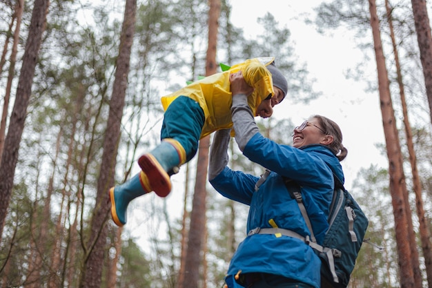 Famille heureuse maman et enfant marchant dans la forêt après la pluie dans des imperméables ensemble, maman jette l'enfant dans le ciel