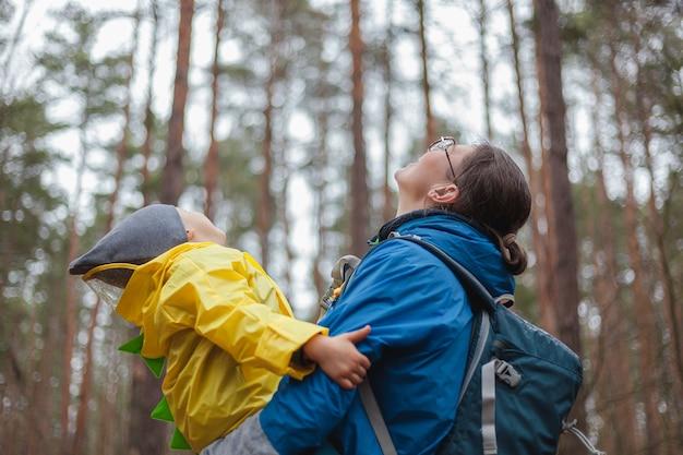 Famille heureuse maman et enfant marchent dans la forêt après la pluie en imperméables ensemble, s'embrassent et regardent le ciel
