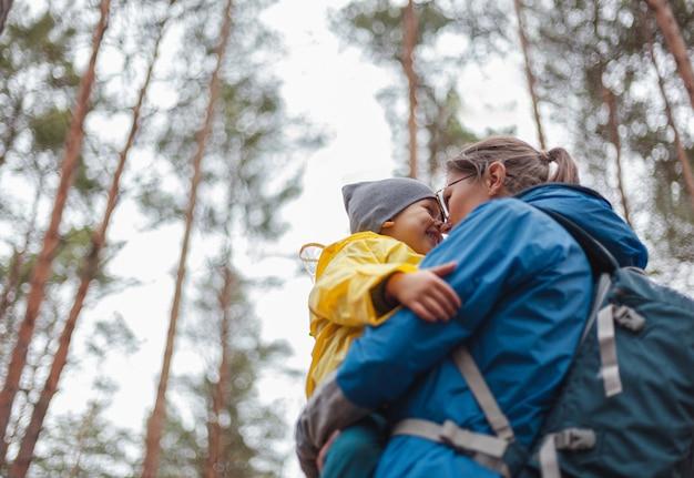 Famille heureuse maman et enfant marchent dans la forêt après la pluie en imperméables ensemble, s'embrassent et se regardent