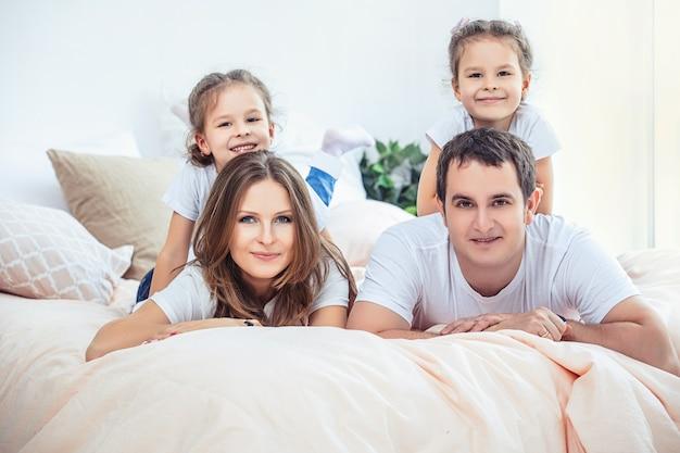 Famille heureuse maman, papa et deux filles sœurs jumelles à la maison dans la chambre sur le lit.