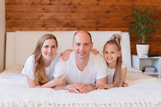 Famille heureuse, maman, papa et fille au lit à la maison dans la chambre