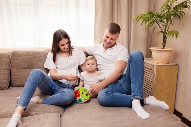 Famille heureuse, maman et papa jouent avec la petite fille, passent du temps ensemble