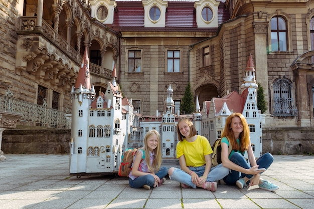 Famille heureuse - maman et ses deux filles sont assises dans un pré beau château en arrière-plan