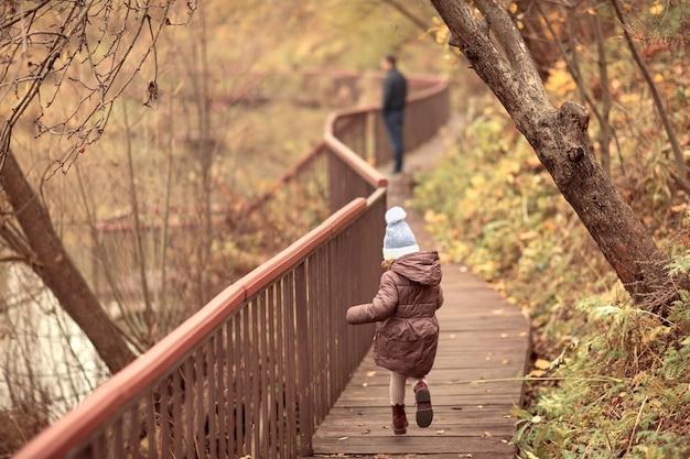 Famille heureuse marchant dans le parc d'automne fille court au père dans naturehello septembre