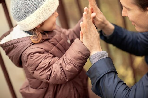 Famille heureuse marchant dans le parc d'automne fille jouer avec père dans natureseptembreselective focus