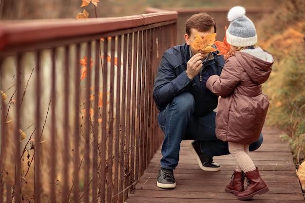 Famille heureuse marchant dans le parc d'automne fille et père jouent avec des feuilles d'érable dans la nature
