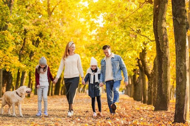 Famille heureuse marchant dans le parc d'automne