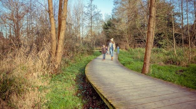 Famille heureuse marchant ensemble tenant des mains au-dessus d'une voie en bois dans la forêt