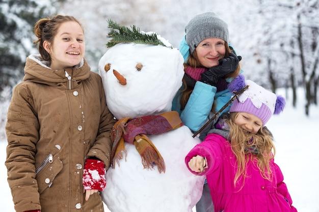 Famille heureuse - mère et filles souriantes avec bonhomme de neige à la journée d'hiver