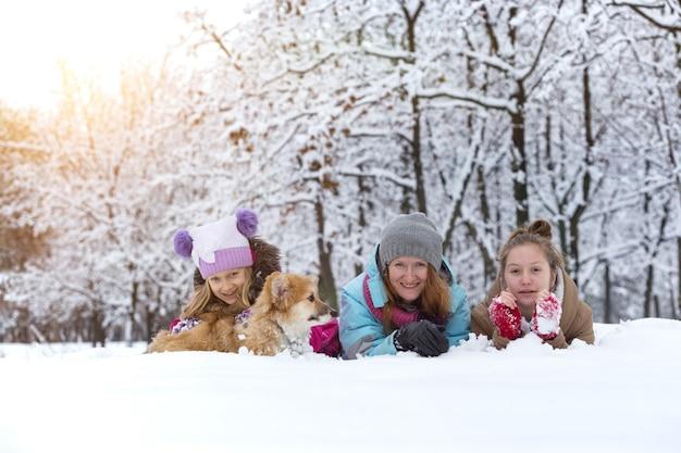 Famille heureuse - mère et filles souriantes avec petit chiot moelleux corgi mignon à la journée d'hiver