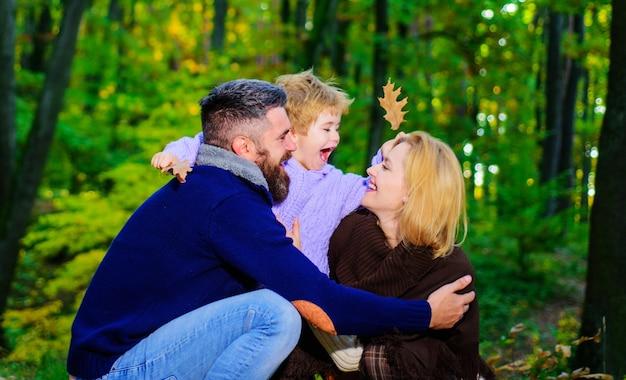 Famille heureuse. mère, père et fils en automne marchent dans le parc. parents et enfants se détendre ensemble en journée ensoleillée.