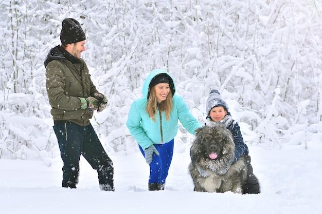 Famille heureuse: mère, père, fils et leur gros chien dans une forêt d'hiver enneigée.