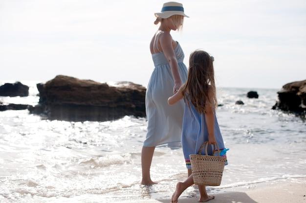 Famille heureuse - mère et petite fille faisant de la randonnée près de la mer
