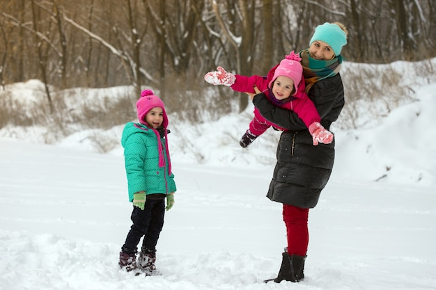 Famille heureuse - mère souriante et petites filles à la journée d'hiver