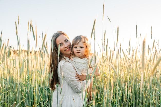 Famille heureuse, mère vêtue d'une robe avec un petit bébé mignon sur un champ de blé doré au coucher du soleil. jour d'été.