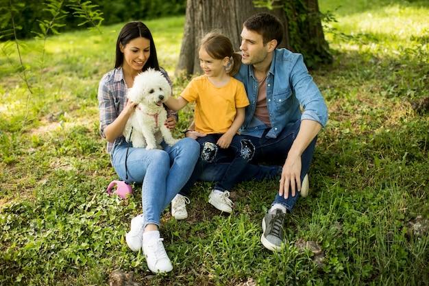 Famille heureuse avec mignon chien bichon dans le parc