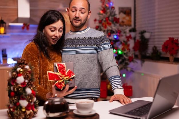 Famille heureuse montrant un cadeau avec un ruban dessus pendant un appel vidéo en ligne