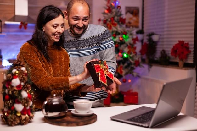 Une famille heureuse montrant une surprise de noël à des amis éloignés lors d'un appel vidéo en ligne