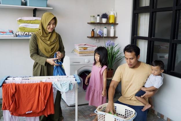 Famille heureuse musulmane faisant la lessive à la maison ensemble