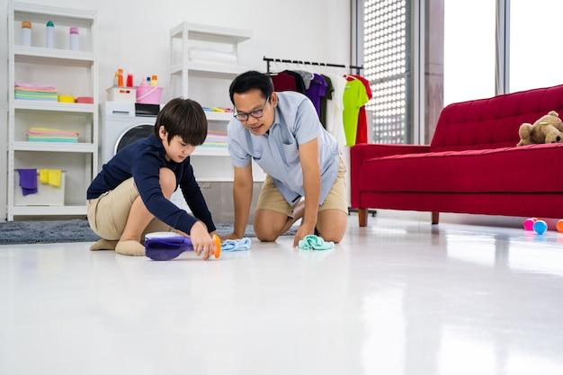 Une famille heureuse nettoie la chambre un père et un fils asiatiques font le ménage dans la maison