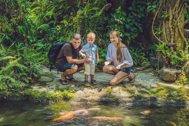 Famille heureuse nourrir le poisson-chat coloré dans un étang tropical