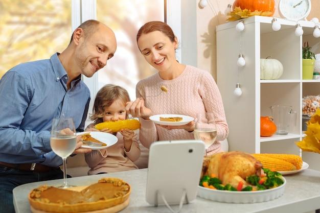 Une famille heureuse organise un dîner de thanksgiving et envoie un message vidéo à ses parents par internet.