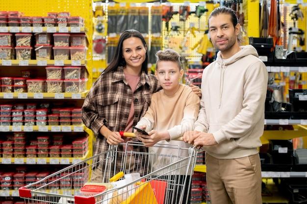 Famille heureuse avec panier dans un supermarché de matériel
