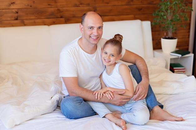 Famille heureuse, papa et fille câlins au lit. joyeuse fête des pères