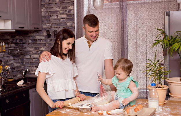Famille heureuse, papa, maman et fille jouent et cuisinent dans la cuisine, pétrissent la pâte et préparent des biscuits