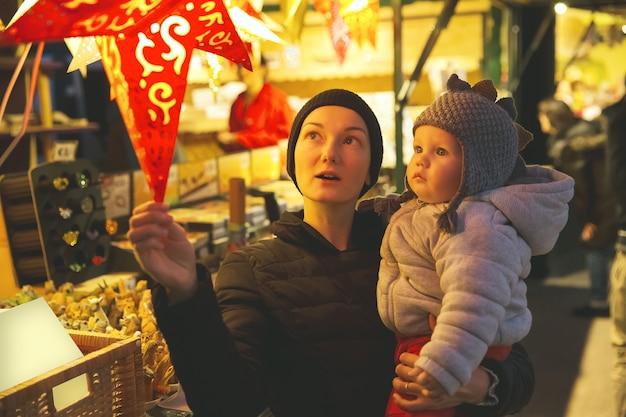 Une famille heureuse passe du temps à une foire du marché de rue de noël dans la vieille ville de salzbourg en autriche