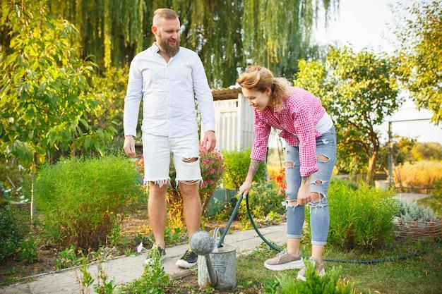 Famille heureuse pendant l'arrosage des plantes dans un jardin