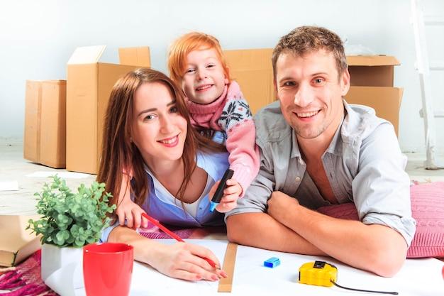La famille heureuse pendant la réparation et le déménagement
