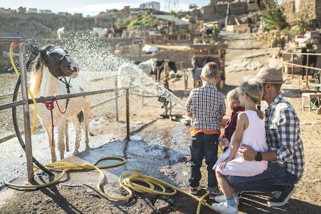 Famille heureuse avec père et enfants lavant leur cheval en plein air à la ferme du ranch
