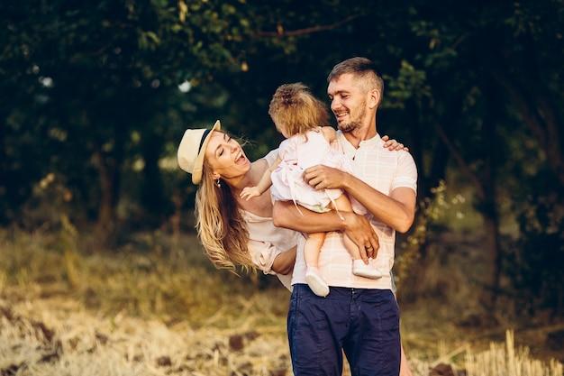 Famille heureuse. père, mère et fille dans le parc