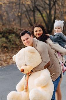 Famille heureuse avec petit bébé promenade au parc, arbres jaunes à l'automne