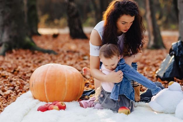 Famille heureuse avec petit enfant mignon dans le parc sur une feuille jaune avec grosse citrouille en automne