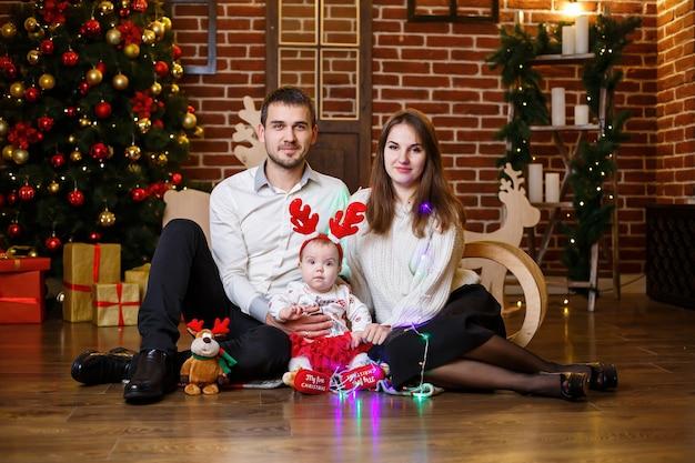 Une famille heureuse avec un petit enfant se tient près d'un arbre de noël avec des jouets et des cadeaux. enfance heureuse. ambiance festive du nouvel an. notion de relation familiale