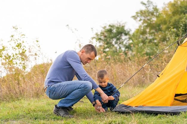 Famille heureuse avec petit fils mis en place une tente de camping. enfance heureuse, voyage de camping avec les parents. un enfant aide à monter une tente