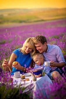 Une famille heureuse avec un petit garçon marche et joue sur un magnifique champ de lavande. vacances en famille.