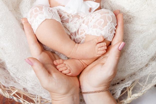 Famille heureuse . pieds de bébé nouveau-né dans les mains de la mère en blanc