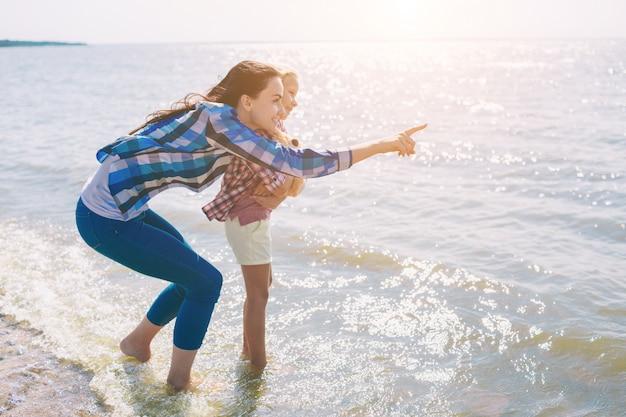 Famille heureuse sur la plage. les gens s'amusent en vacances d'été. mère et enfant sur fond bleu de mer et de ciel. concept de voyage de vacances