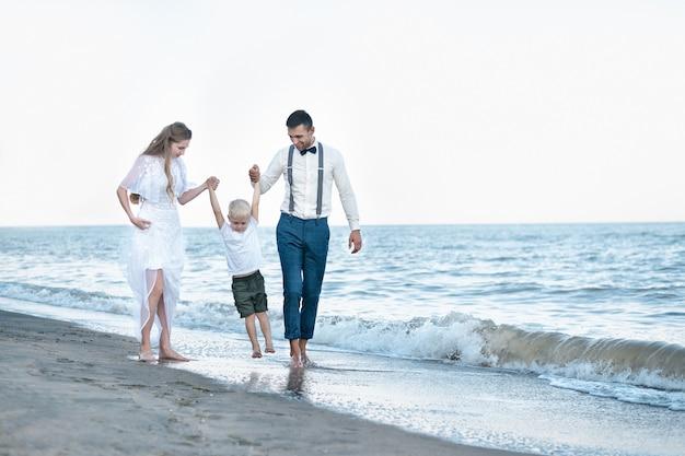Famille heureuse sur la plage de la mer au resort. mère et père lèvent les mains du fils. vacances en mer avec des enfants