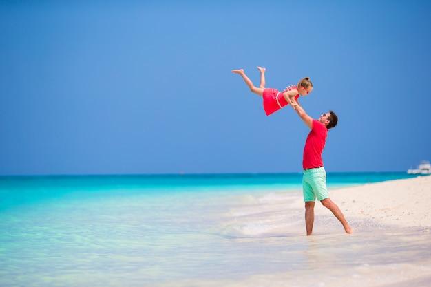 Famille heureuse sur la plage tropicale s'amuser